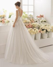 Denne brudekjole har dyb ryg, knaplukning og fyldigt skørt med slæb.