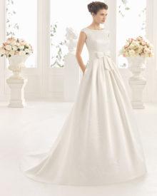 Brudekjole i satin med lille ærme, sløjfe og fyldigt skørt.