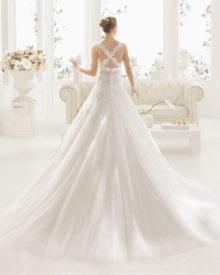 Brudekjolen har krydsende blondestropper, bælte og slæb.