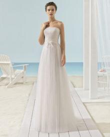 Stropløs brudekjole med draperet top, blonde bælte og plisseret tylskørt.