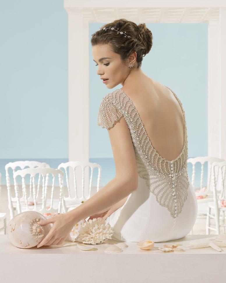 Xiana har dyb ryg med smukke perler samt lille ærme.