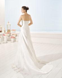 Brudekjole i chiffon med snørereryg, draperinger samt slæb.
