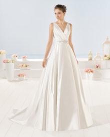 Yvonet brudekjole i satin med V-skæring, draperinger, blondebelagt bælte og fyldigt skørt.